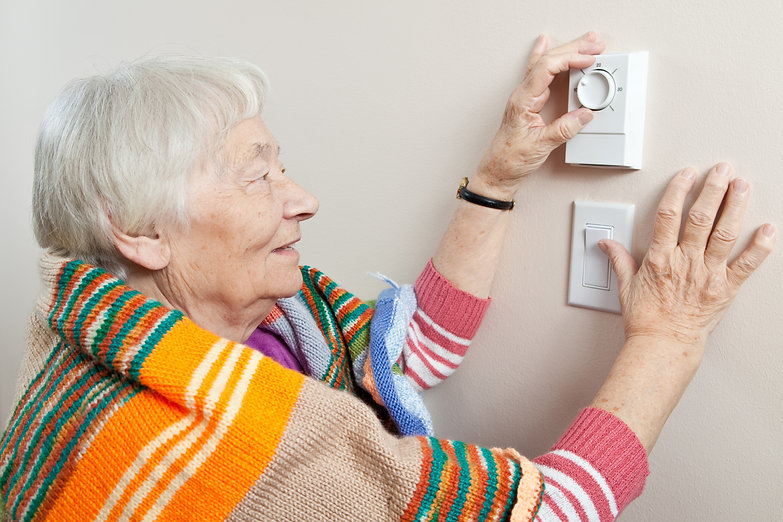 Older lady adjusting thermostat.jpg