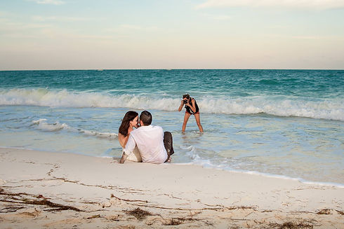 girl photographer taking a photograph in the ocean on a beach of a wedding bride and groom in the sand