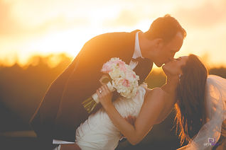 wedding bride and groom bent over kissing in the sunset