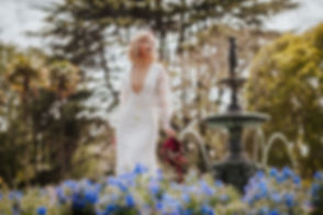 fashion photograph of a bride holding her red shoes infront of a fountain in the flowers