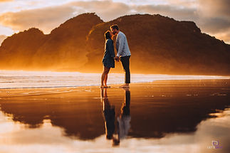 young engaged couple kissing on the beach at sunset with their reflection
