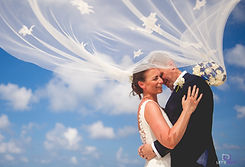 bride and groom with veil hugging under the blue sky