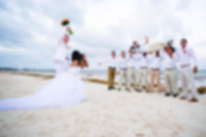 photographer at  beach wedding being lifted by bridal party and bride taking a photograph of the photographer