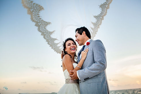 bride and groom smiling at each other on the beach with the veil blowing in the wind