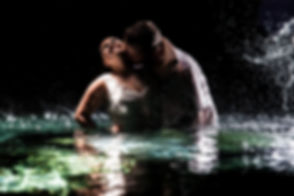 bride and groom in the water splashing and kissing