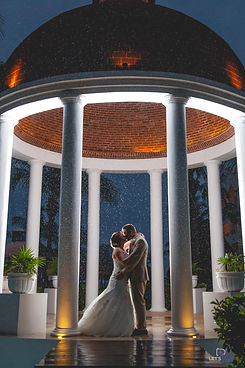 bride and groom kissing in the rain at night time
