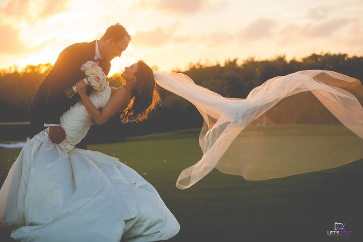 bride and groom leaning over smiling at each other in the sunset with veil blowing