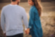 close up of romantic engaged couple holding hands on beach