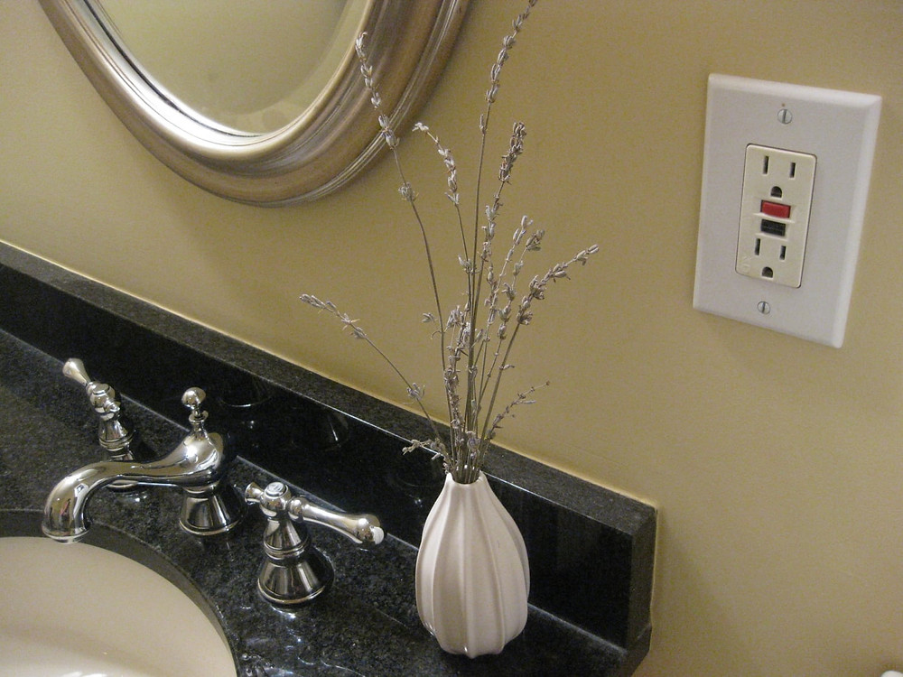 A GFCI outlet installed by an electrician in a bathroom.