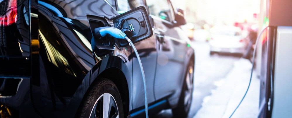 Electric car at a charging station. Learn about home charging stations.