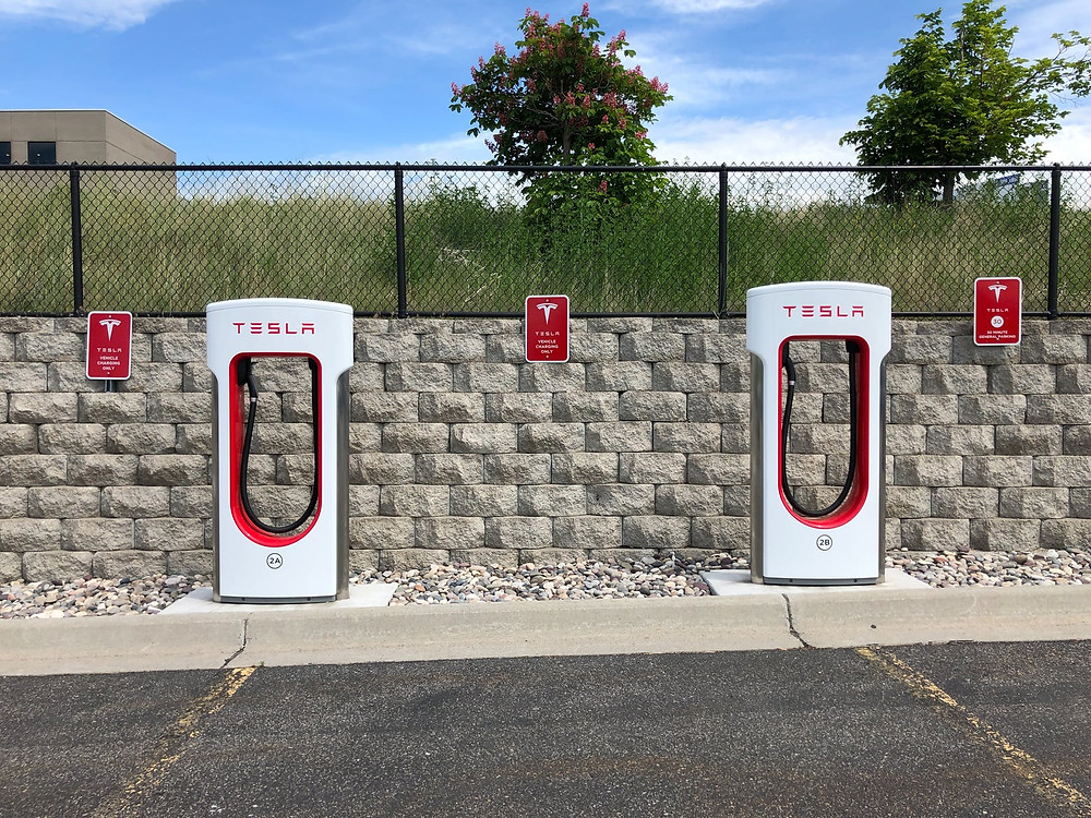 Tesla car chargers in a parking lot.