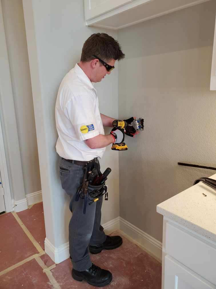 A IES Home Services electrician works on a receptacle,