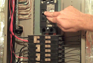 A home electrical panel being working on by an electrician.