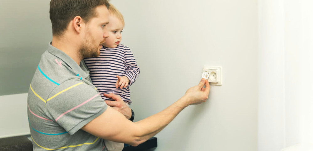A man holds a baby and adds child-proofing to his electrical outlet.