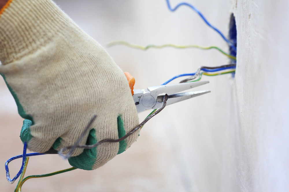 An electrician works with a home's wiring.
