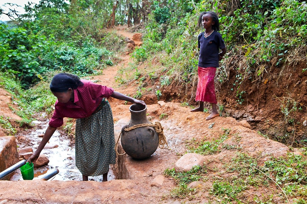 ethiopian woman and girl getting water for their family