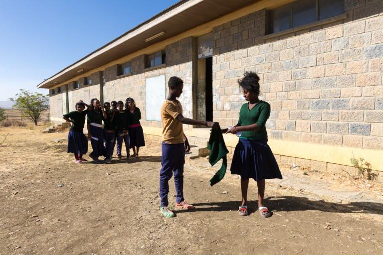 ethiopian boy supporting girl during menstruation