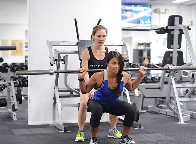 Certified Personal Trainer providing client back squat support