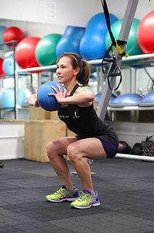 certified personal trainer, head trainer, director of fitness completing squats with a medicine ball
