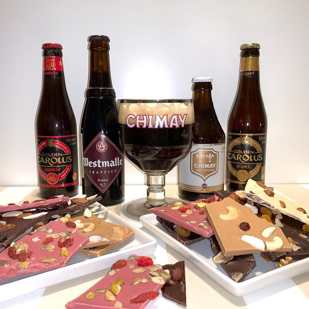 Foto mostra 4 garrafas de cerveja, duas de cada lado de uma taça que está cheia de cerveja escura.