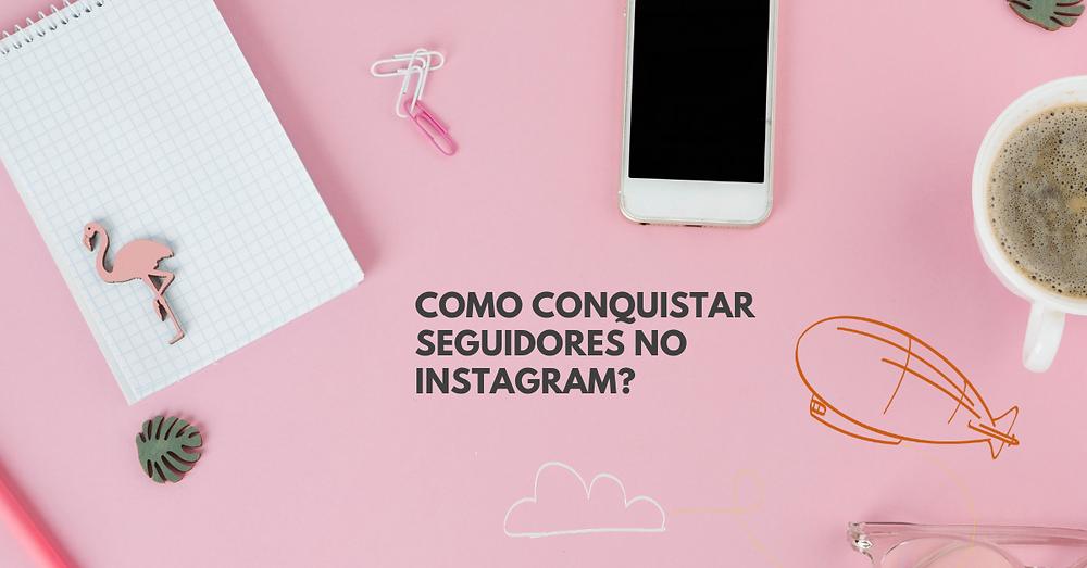 Imagem mostra uma mesa cor-de-rosa fotografada de cima. Sobre a mesa estão um caderno e um telefone celular. No centro da imagem está o título deste post: Como conquistar seguidores no Instagram?