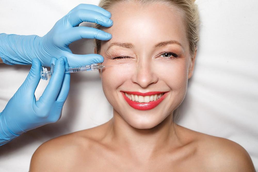 Mulher sorrindo e recebendo no rosto uma injeção de botox