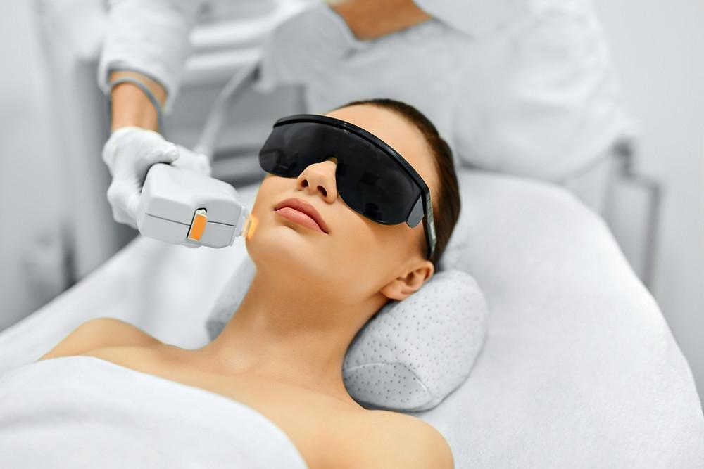 Mulher com óculos escuro recebendo tratamento estético com luz pulsada