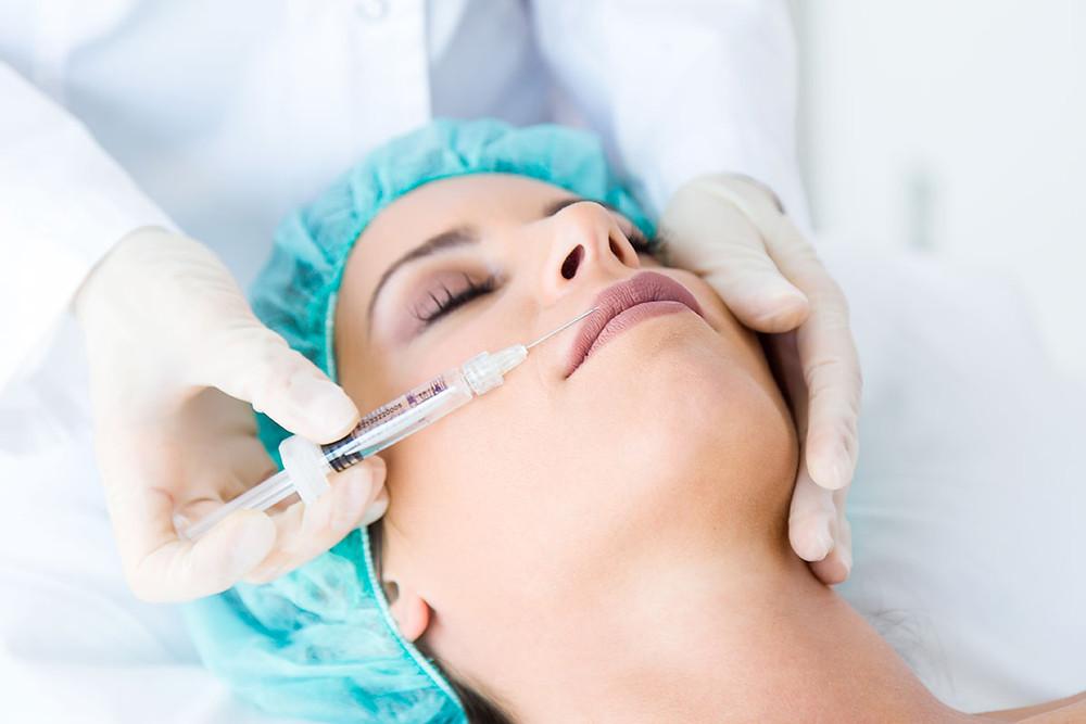 Mulher em uma clínica de estética recebendo injeção no rosto