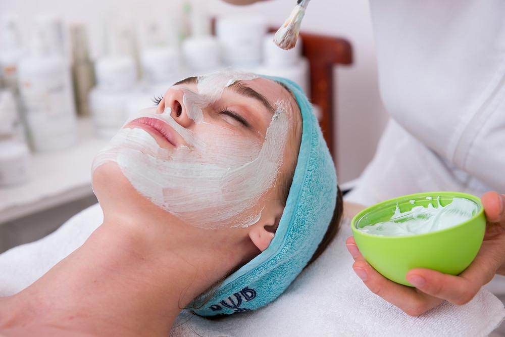Mulher deitada em uma maca fazendo tratamentos estéticos para se manter jovem sem precisar de cirurgia