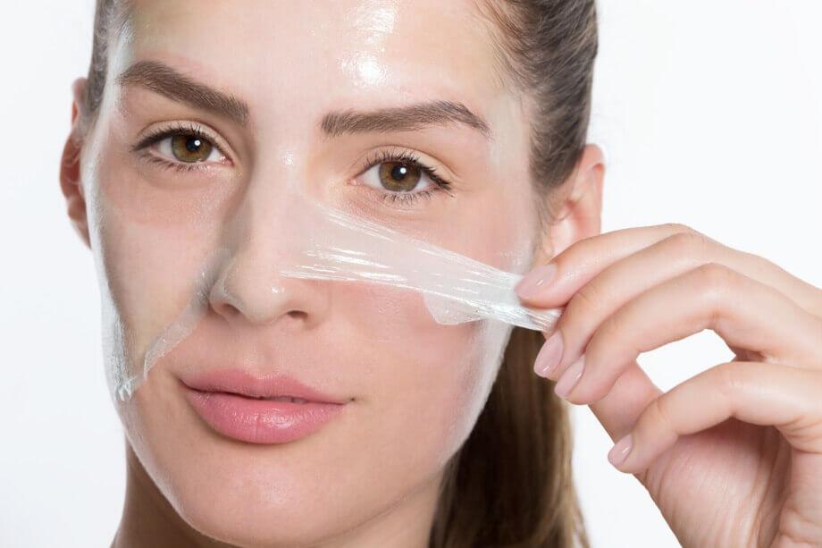 Mulher puxando a máscara de peeling facial do rosto após secar