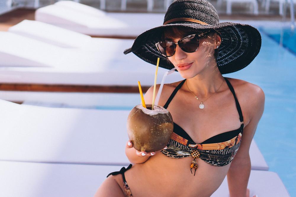 Mulher com biquini, chapéu e óculos de sol tomando água de coco perto de uma piscina