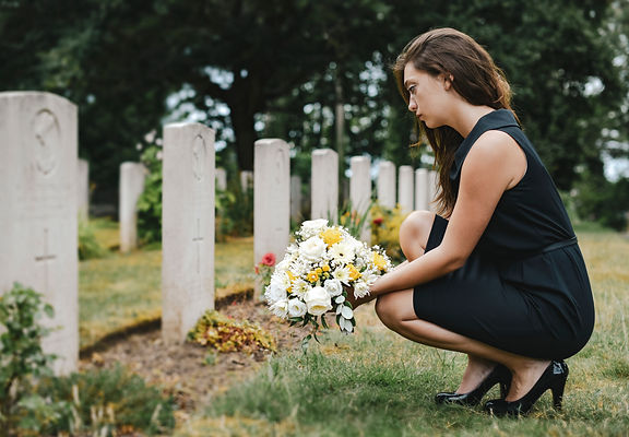 young-widow-laying-flowers-at-the-grave-2021-04-02-19-57-20-utc.jpg