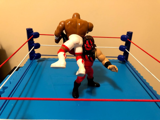 Kane lifts Virgil over his head to deliver a biiiiiiiiig chokeslam!  It may be all over for Virgil now, as the elimination appears to be elementary.  But wait.... we're about to introduce our next competitor! Three.... two.... one... and it's....