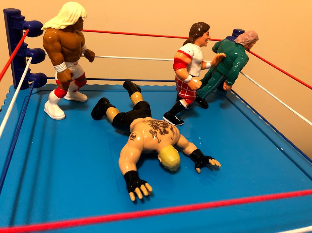 Piper has come to Virgil's aid, similar to what he did at WrestleMania VII (though Virgil wasn't wearing a wig at the time). Piper elbows Lesnar in the face and pokes DiBiase in the eye. Hot Rod is trying to eliminate the Million Dollar Man!