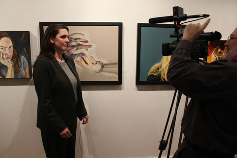 Artist being filmed in front of her work