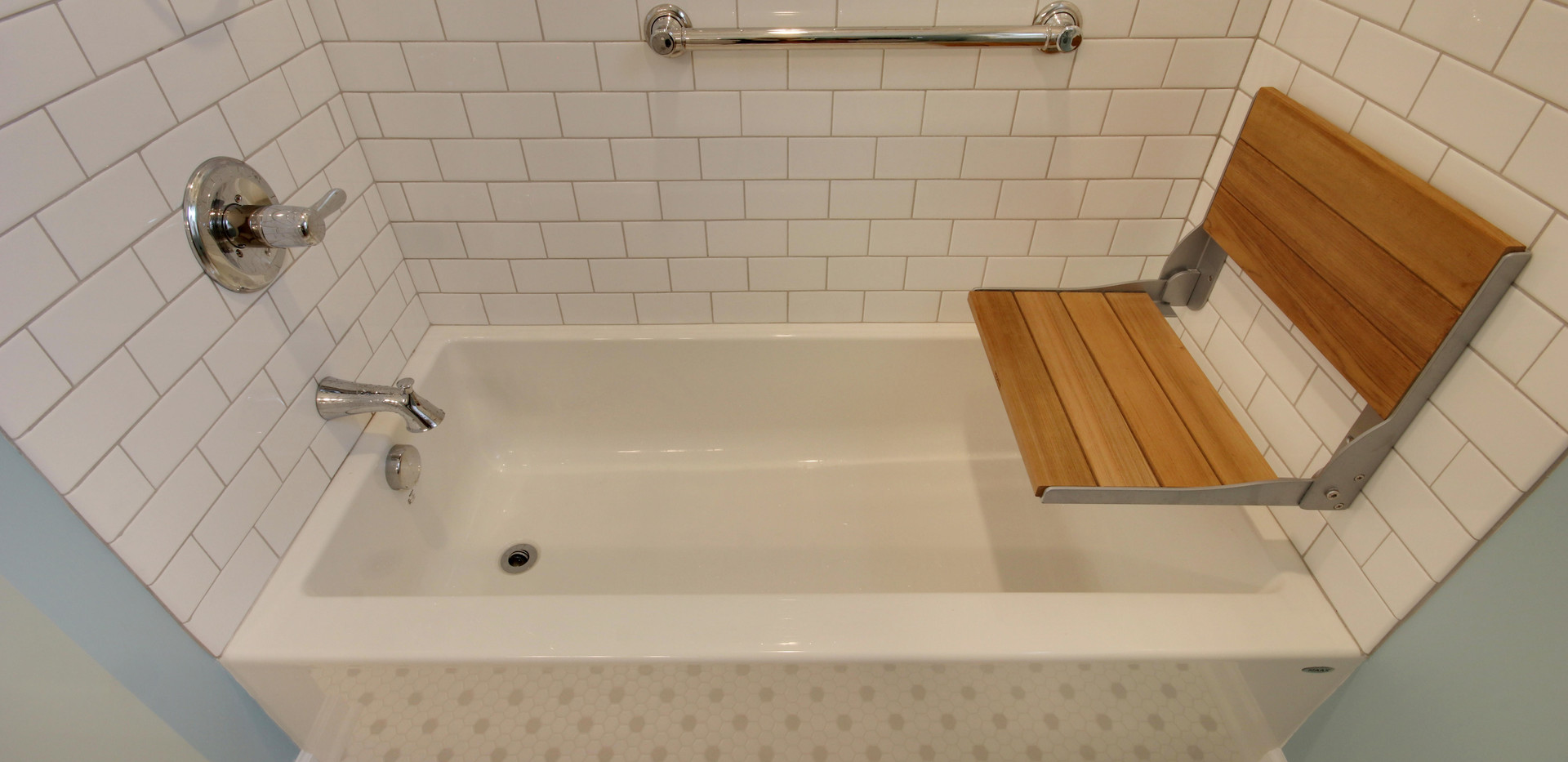 New tub shower bathroom remodel featuring a wood shower bench, grab bars, and white tile