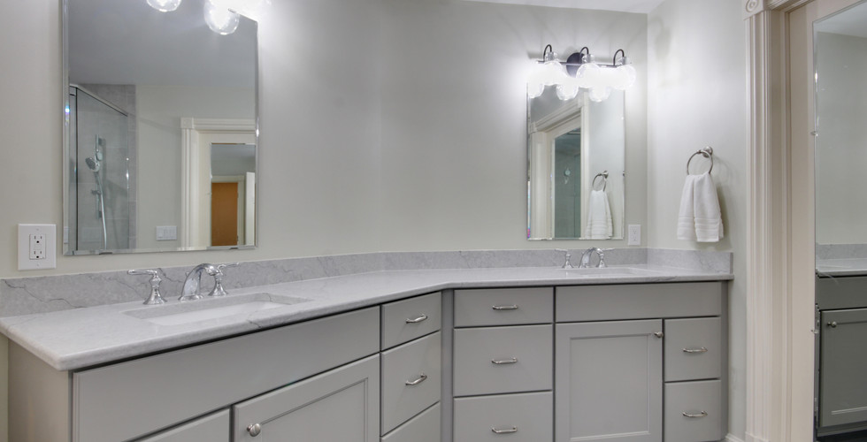 Long bathroom vanity with two sinks featuring white drawers and cabinet space