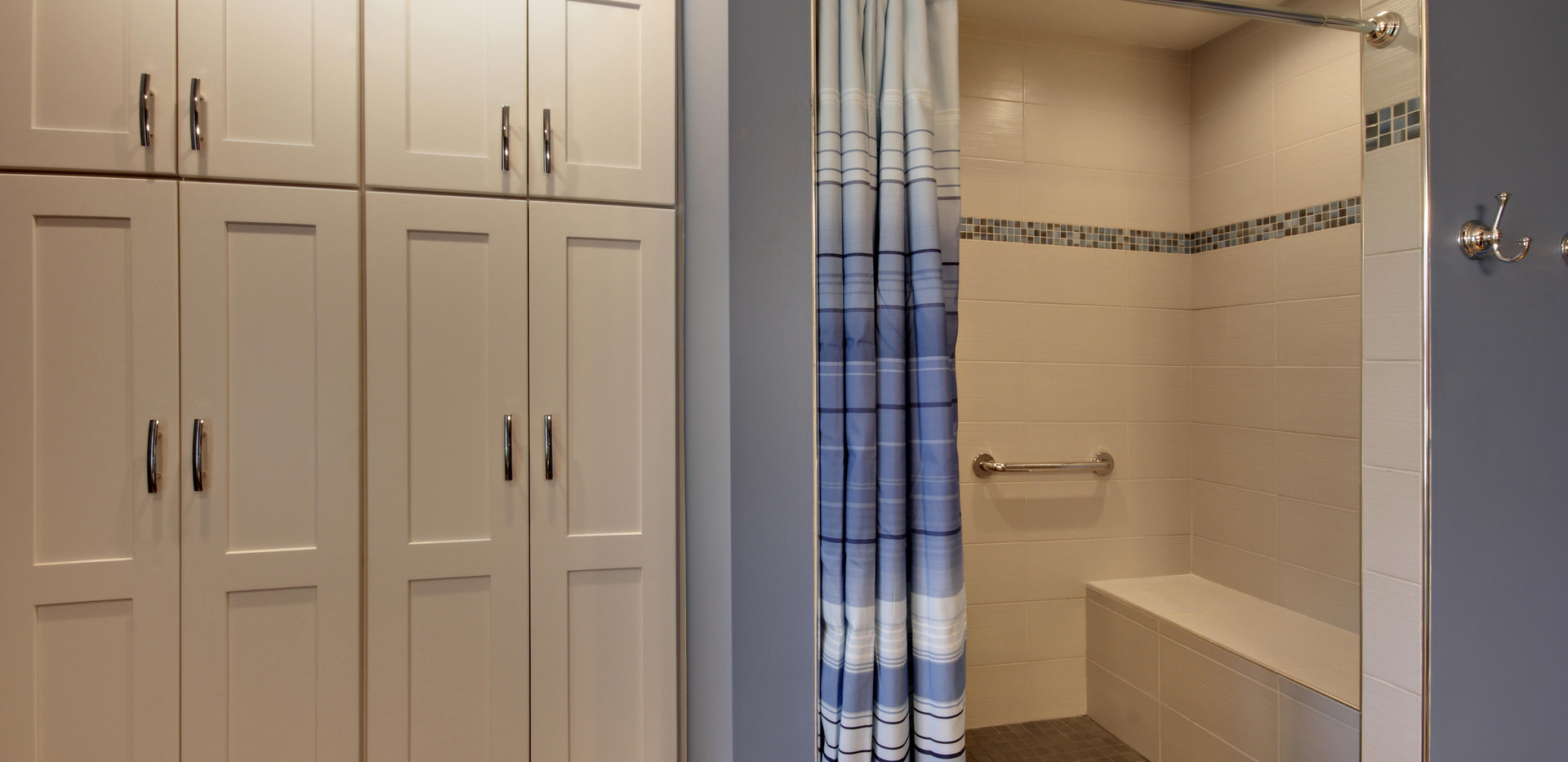 View of white cabinet space and new tile shower of Hudsonville bathroom remodel by Renew Home Improvement
