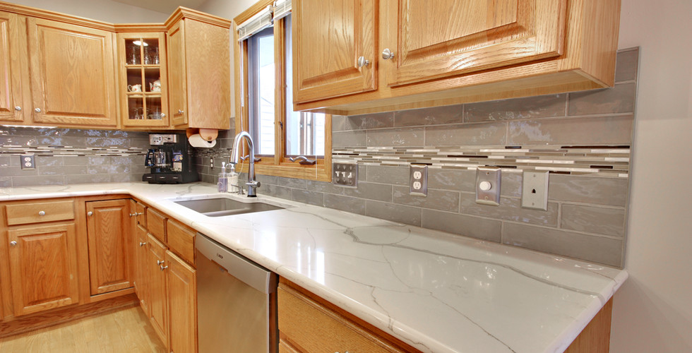 Full view of sink area space featuring new white granite counter tops
