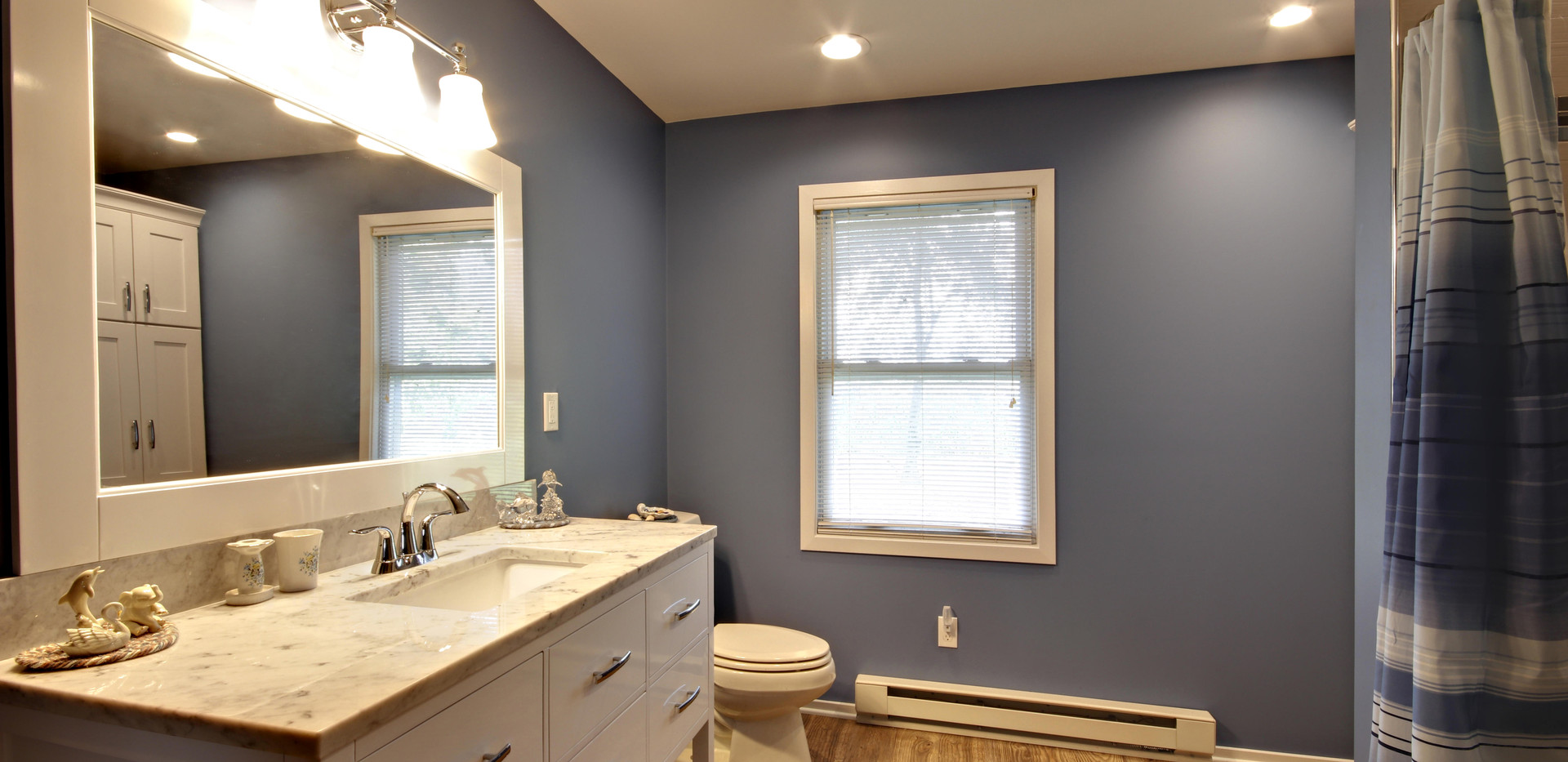 Hudsonville bathroom remodel project featuring new vanity, paint, tile shower with grab bars, and cabinet space
