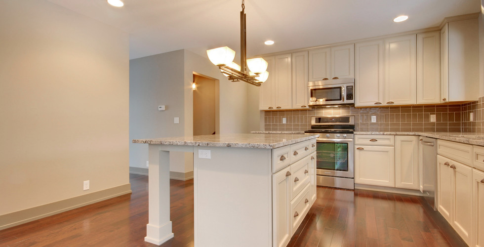 Full view of kitchen remodel featuring wood floors, new island, sink, appliances, and more