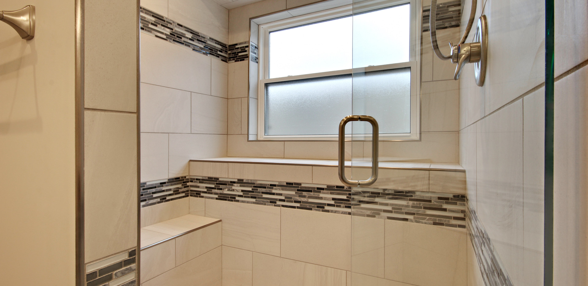 Jenison traditional shower remodel featuring a glass door, tile bench, and white tile