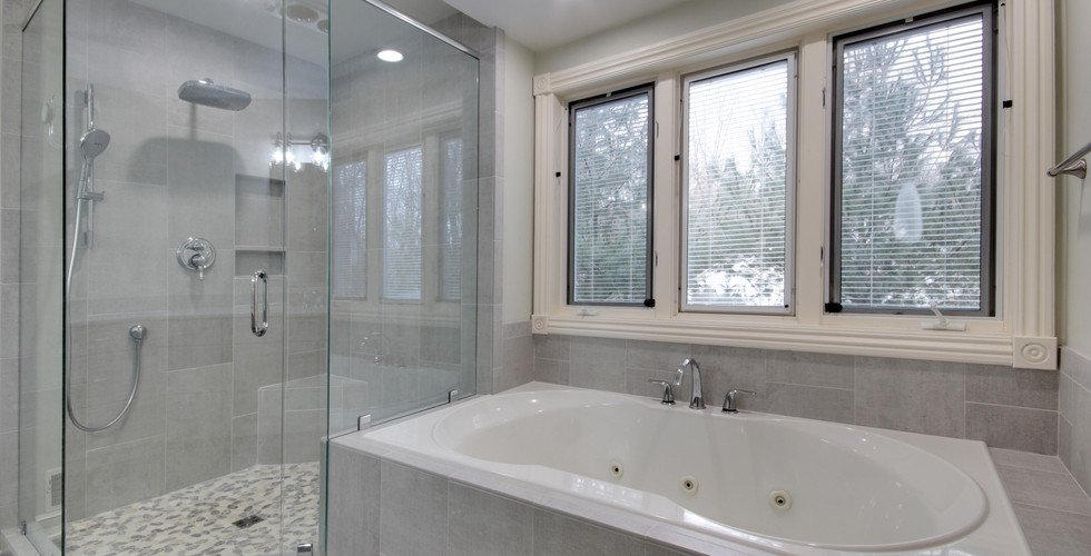 New tile shower with glass doors and spa area of Grand Haven bathroom remodel