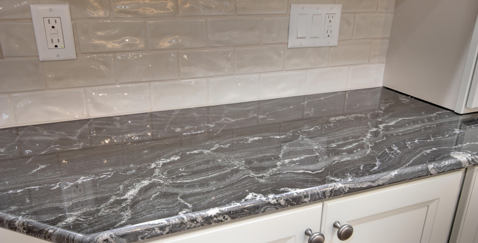 New kitchen counter top space featuring black granite and white tile back splash