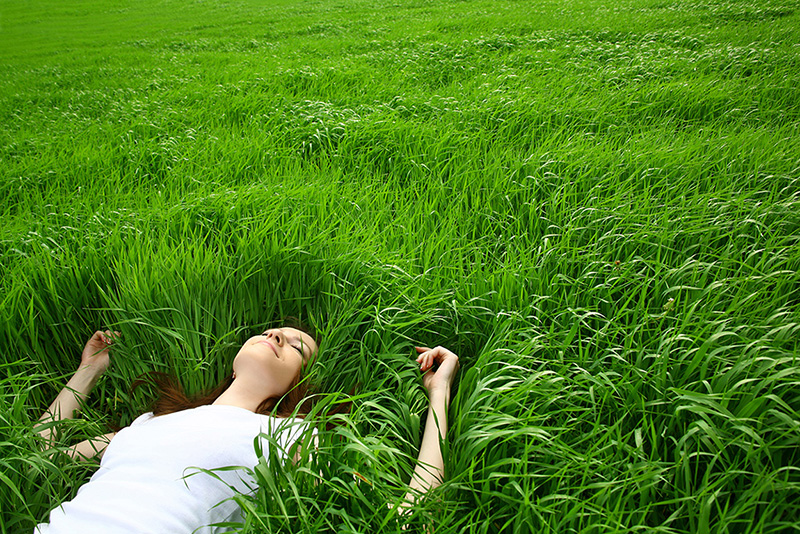 Girl lying in the grass. Re:Down: powerful organic fertilizer for a greener world!