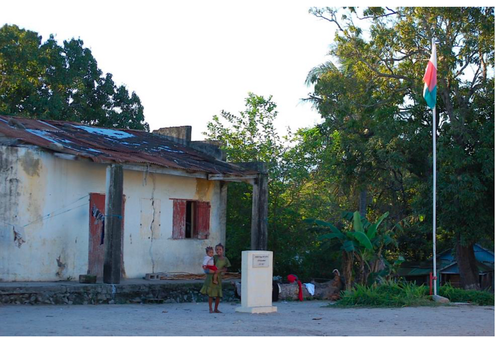 A crumbling school with an older child holding a smaller child outside of it