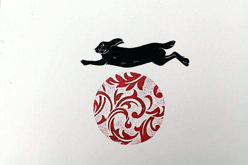 Hare leaping over a red ball