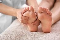 Frauenhände behandeln Reflexzonen der Füße