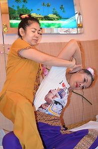 Thailänderin führt durch die Thai Massage Dehnbewegungen durch