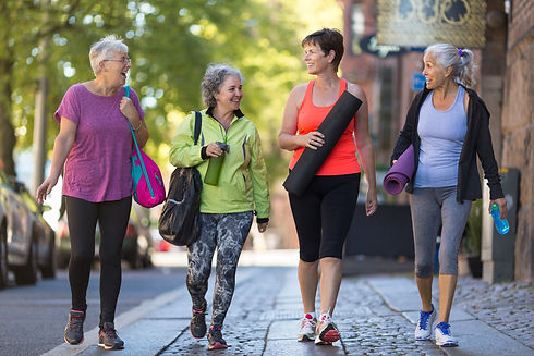 Four women walking on the sidewalk. They are carrying athletic gear like yoga mats and water.